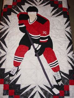 Closeup of the hockey player quilt. I put my son's jersey number on it for him. Notice that the quilting stitching is sticks and pucks. I had someone machine quilt that for me.