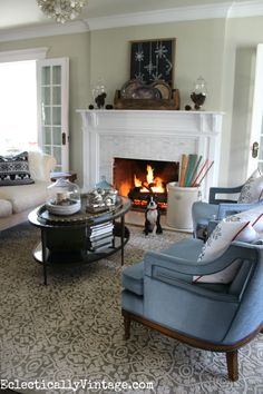 Cozy winter decorating ideas - love the rustic mantel and the roaring fire with apothecary jars from HomeGoods filled with pinecones eclecticallyvintage.com HomeGoodsHappy HappyByDesign sponsored
