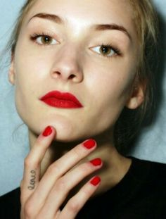 "matching red lips and nails plus ""love."" interestingly with a full stop after it, as kind of a (whatever word has been chosen) is all that matters subtle statement, on inner finger"