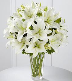 Two bouquets of white lilies at the church altar but in opaque vintage style urns.