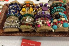 DIY Bracelet display for craft shows. Wrap cotton fiber with material about the size of your wrist. Put bracelets around wrap and place them in a dish for show.