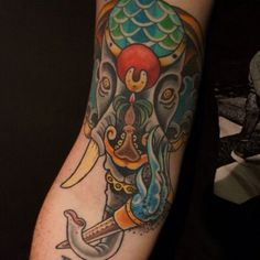 24. Bizarre splendor on the half sleeve A surreal colorful tattoo covers the half sleeve, the elephant has many embellishments on the head and a torch in its trunk. The symbolism discloses the idea of prosperity, self-improvement, and exceptional luck. - source