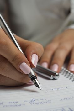 Woman in White Long Sleeved Shirt Holding a Pen Writing on a Paper