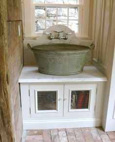 galvinized bucket sink, farmhouse style with chicken wire covered cabinets.