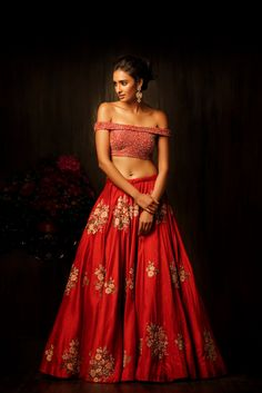 This ultra-modern red lehenga has a tango red bias cut raw silk lehenga, ornamented with uniquely crafted buttas done in resham thread, zardosi, peeta and tikkis. Paired with an off shoulder blouse fully encrusted with pearls, sequins and crystals and a new wheat tulle dupatta with a heavily ornamented border, this lehenga is luxurious and stylish, appropriate for any wedding occasion. #bridal #trends #bridal2017 #bridalfashion #bridaldress #weddinglehenga #offshoulder