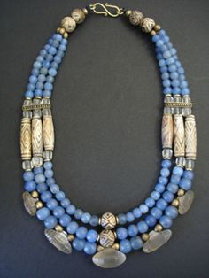 By Luda Hunter | 'Burma Blue'.  Blue glass beads from Burma, 12 antique early 20th century clay beads from Tibet/Nepal, 5 old Rock Crystal pendant beads in varying sizes from the African trade and Bohemian Czech rare and old 1900's cube glass beads. Scattering of Nigerian brass beads and spacers and the necklace is finished with a gold vermeil clasp | 440$
