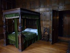huge old wooden four-poster bed and wood panels