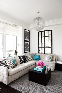 Contemporary living room features a clear beaded chandelier illuminating a light grey crushed velvet sofa adorned with gray pillows, black pillows and turquoise pillows facing a black lacquered block coffee table topped with a turquoise tray atop a gray pebbled rug.