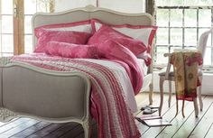 All White Bedroom With Bright Pink Bedlinen on neutral colored bed make it look right