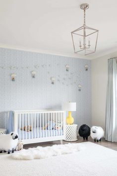 Gorgeous blue and white nursery features a white crib dressed in blue bedding and draped with a blue throw that beautifully complements a blue wallpapered accent wall accented with hot air balloon decor. Striped Nursery, White Nursery, Nursery Room, Lamb Nursery, Pastel Nursery, Babies Nursery, Nursery Curtains, Nursery Decor, Bedroom Decor