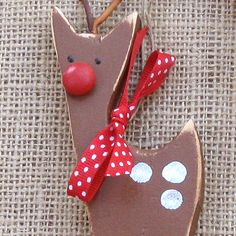 Rudolf the Red-nosed Reindeer is a wooden Christmas ornament, hand-cut, hand-painted and decorated with twig antlers, a red nose, white spots and a