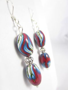These handmade polymer clay tear drop earrings feature a gradient of pink, blue and white polymer clay accented with interwoven stripes of black and yellow. Each earring features two oval polymer clay beads separated by a round antiqued silver corrugated metal bead that is attached to a flat silver plated earring hook. The oval polymer clay beads are coated in water based glossy varnish for high shine…
