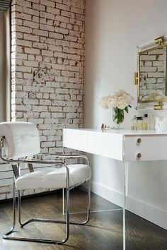 Dressing room featuring whitewashed exposed brick walls alongside a white…