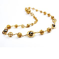 Rotating armillary sphere necklace: 18ct gold and tahitian pearls   Photo: Simon Carr