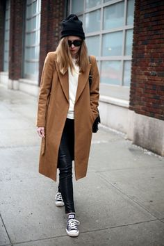 Shop this look for $217:  http://lookastic.com/women/looks/crew-neck-sweater-and-leggings-and-low-top-sneakers-and-beanie-and-overcoat/1040  — White Crew-neck Sweater  — Black Leather Leggings  — Navy Low Top Sneakers  — Black Beanie  — Tobacco Coat