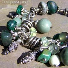 This lovely artisan handcrafted Sterling silver bracelet combines beautiful jade, turquoise and other lovely green gemstones into a one-of-a-kind piece of wire art jewelry.