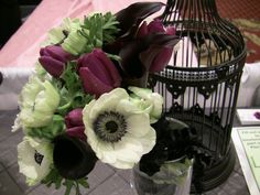 Bridal bouquet of white and black anemone, black calla lilies, purple tulips and white parrot tulips.