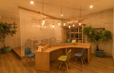 Organic-shaped wooden co-working spaces with brightly coloured custom Eames chairs. Above the table is a lamp built with an assembly of mason jars. Seen in the background are vertical wooden bars that form a visual separator.