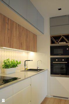 Prosta zabudowa kuchenna - gładkie fronty w bieli i szarości ożywione naturalną okleiną drewnopodobną - zdjęcie od Dizajnia art - studio projektowe - Kuchnia - Styl Skandynawski - Dizajnia art - studio projektowe
