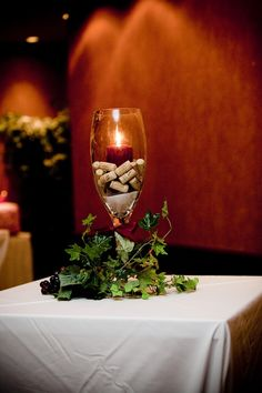 """So I have giant wine glasses for my center pieces and wanted to have the flower either inside on on top and fill the glass with corks like this...Wine-theme"""" Wedding Centerpiece 