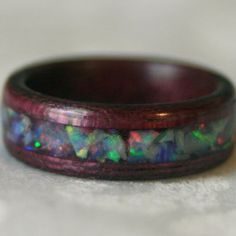 Custom ring made with Purpleheart wood and an inlay of crushed Opal... I totally love this guy's stuff!!!  by MnMWoodworks