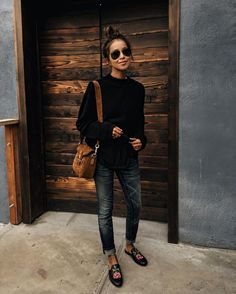 Faded black jeans, sweat, loafers, tan bag
