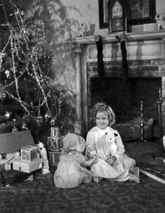 1936: American child actor Shirley Temple sitting by her decorated Christmas tree with presents from 20th Century Fox, 1936. Stockings are hung from the mantel behind her.
