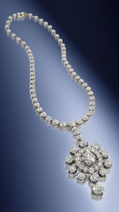 An antique diamond pendant/necklace, 19th century. The detachable pendant/brooch of highly stylised flowerhead design, with a central pear-shaped diamond weighing 3.29 carats within a surround of similarly-cut diamonds, terminating in a large cushion-shaped diamond drop, suspended from a rivière of fifty-nine cushion-shaped diamonds, graduating in size from the centre, additional brooch fittings, diamonds approximately 36.85 carats total, lengths: necklace 41.0cm, brooch 6.4cm. #antique