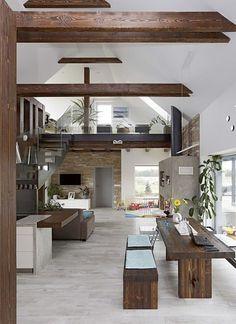 """Celkový pohled na obytnou místnost. Citlivě a se vkusem se tu prolínají dva styly: nadčasový """"chladnější"""" design a venkovské prvky: přiznané dřevěné trámy, masivní stůl a lavice, obkladový kámen."""