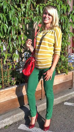 nice outfit with green jeans and pops of red