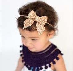 Rose gold glitter bow on one size fits all nylon elastic.