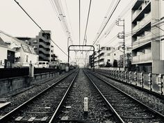 Grayscale Photography of Train Rail Between Buildings  Free Stock Photo