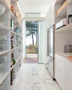 Plastic laminate and ApplePly open shelving in kitchen, carrara marble tiles on floor, North Beach House on Orcas Island by Heliotrope Architects, Remodelista