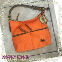 """Dooney and Bourke NWOT So cute! Perfect condition!! Orange Dooney and Bourke length 9 1/2"""" strap drop 8 1/4"""" depth 5"""" height 7 3/4"""". Nylon material hobo style. One main pocket two smaller pockets in front. Bought it because I HAD to have it but I am not much of a purse person so it has been in my closet ever since . Just an awesome purse that deserves to be shown off! Dooney & Bourke Bags Hobos"""