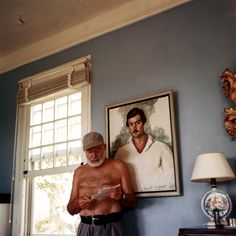 EH-C00176T Ernest Hemingway in front of his portrait at his home, Finca Vigia, San Francisco de Paula, Cuba, circa 1953.