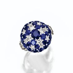 SAPPHIRE AND DIAMOND RING-WATCH, CARTIER, NEW YORK, CIRCA 1940. The circular dial concealed by a hinged dome decorated in a starburst motif with round and oval sapphires and round diamonds, flanked by diamond-set scroll shoulders, the total diamond weight approximately 1.30 carats, mounted in platinum, dial signed Cartier, numbered 5885, movement by Glycine Watch Co.