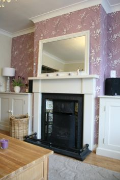 Client requested colour to brought into the room and extra storage, I used Laura Ashley Pussy Willow wallpaper on the feature wall, I also got a carpenter to build the storage in the alcoves.  Suzanne Smith Interiors - find me on Facebook.