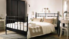 Chambre B&B avec lit noir et linge de lit beige/blanc