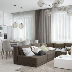 Студия LESH | Большая кухня-гостиная оформлена в белом цвете, на этом контрастно смотрится угловой диван темного земельного цвета