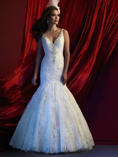 STYLE: C361  This couture lace gown features a mermaid silhouette and trailing gemstones along the neckline.