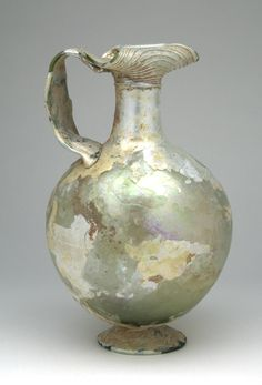 "A Choice Ewer, in Pale Green Glass. Roman 3rd to 4th century AD. Height: 9-1/8"". Blown from leaf green or yellow-green glass, this elegant vessel features a trefoil-folded funnel mouth, and a broad cylinder neck on an almost spherical body all of which sit atop a curved and flaring folded foot. $4,715"