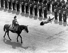 As Queen Elizabeth II rides by during the Trooping the Colour Ceremony at Horse Guards today one guard, overwhelmed by the heat, faints in the path of the oncoming Queen  14th June 1969