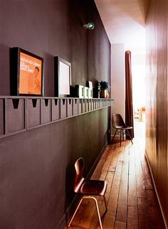 Le couloir aubergineLes couloirs étroits sont toujours des espaces difficiles à aménager. Le choix d'une couleur forte, comme ici, ce beau marron foncé, permet toujours d'habiller et de créer une surprise. L'ouverture sur une pièce blanche, au fond du couloir, apporte la luminosité et le contraste nécessaires pour faire vibrer ce coloris sombre.