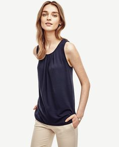"Effortless and elegant, this polished piece flaunts a crisp pleated front in an array of prettily saturated colors. Pleated jewel neck. Sleeveless. Back slit with hook-and-eye closure. Shirttail hem. 25 3/4"" long."