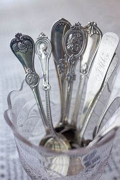 Silver teaspoons in a glass or crystal cup
