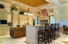 A white and cream kitchen with an eat in bar to the right and a smaller wooden island in natural wood between the cabinets and the eat-in bar. The vent hood and backsplash add a pop of dusky pink color to the design.