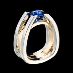 Forte sapphire ring shows strength and structure. This architecturally inspired ring suspends a dazzling blue sapphire in white gold with yellow gold accent. To purchase, call (949) 715-0953 or use our contact form below.   From his Laguna Beach studio, designer and goldsmith Adam