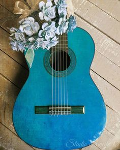 A vintage Broadway Sound guitar in royal blue paired with a bundle of romantic pale blue roses...for the music lover.