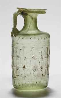 A ROMAN FACET CUT GLASS JUG  CIRCA 4TH CENTURY A.D.