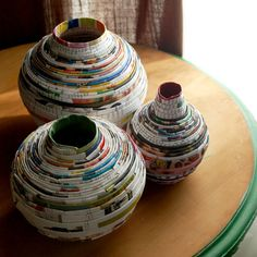 Vases built from coiled magazine pages, sealed with resin so that interiors are watertight.